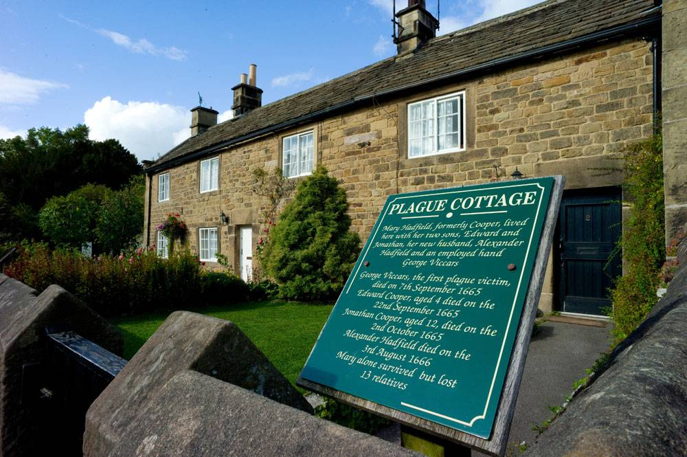 A green sign outside Eyam's 'plague cottage' listing the residents who died during the outbreak