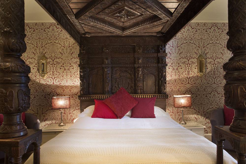 A four-poster bed with red cushions, just one of the George Hotel's luxury rooms