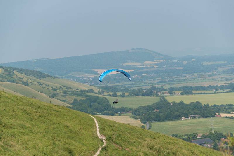A hand glider floats above the green hills of the South Downs