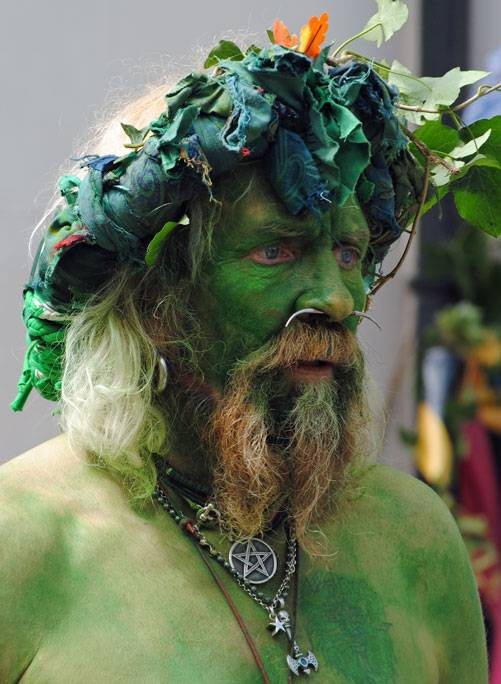 A portrait shot of Jack in the Green who is painted green and wears a garland on his head