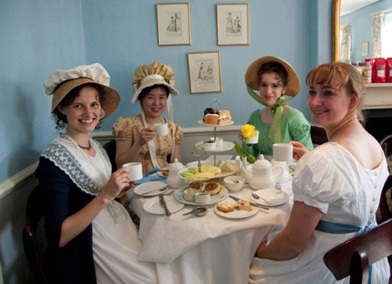 Fans in regency dress having afternoon tea at a table