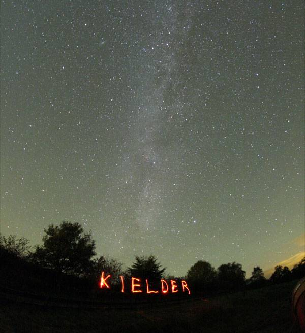 The Milkyway shimmers brightly above the trees of Kielder Observatory