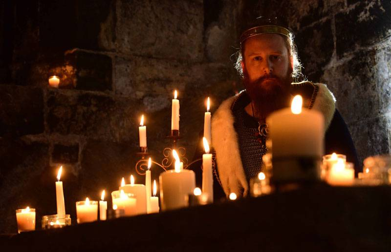 A man dressed as King Canute sits in front of a grand table covered with lit candles