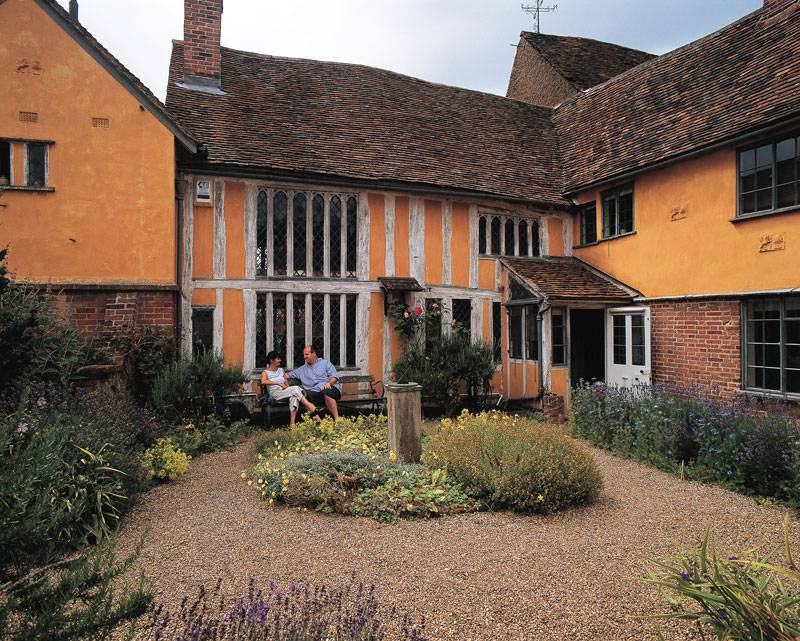 A couple sit in the back garden of a original Tudor house in Lavenham