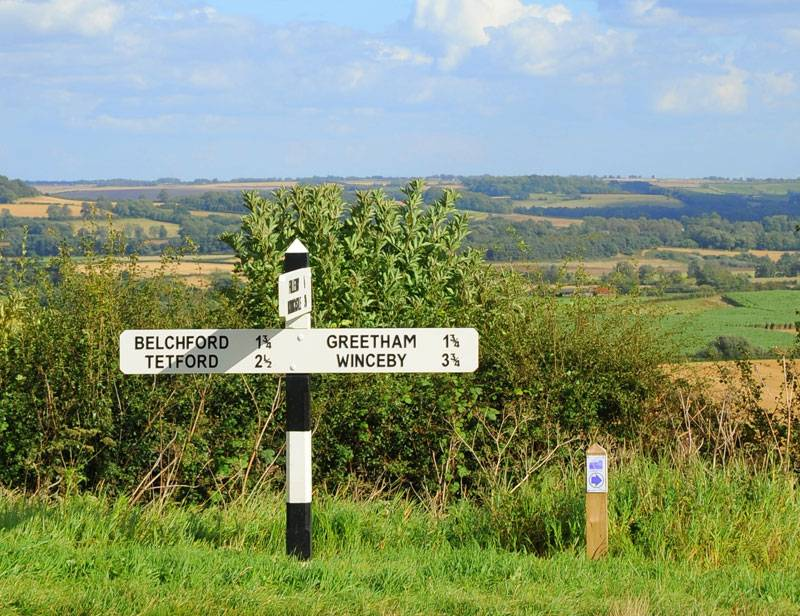 A signpost stands in front of the sprawling green vistas of the Lincolnshire Wolds
