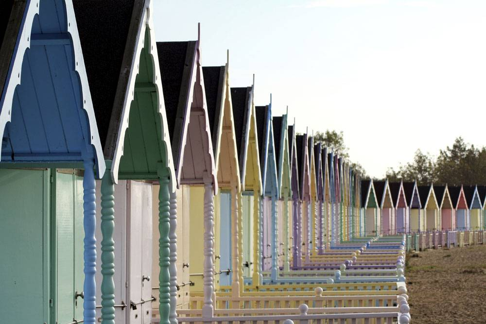 Pastel coloured beach huts lined-up on Mersea Island
