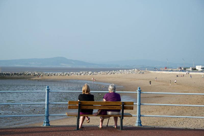 Two women look out to the Lake District in the Distance from Morecambe Bay