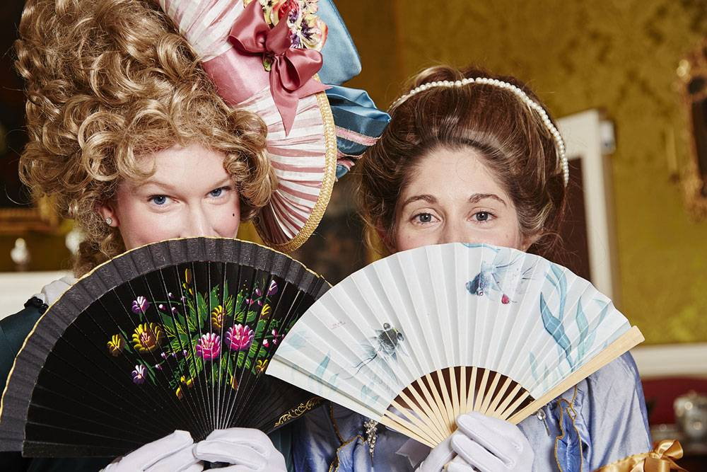Two ladies in georgian fancy conceal their faces with fans