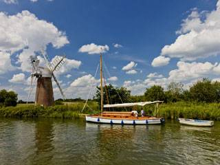 A boat floats along the tranquil Norfolk Broads