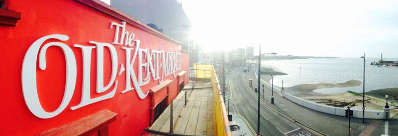 Red signage for the new Old Kent Margate overlooking the beach
