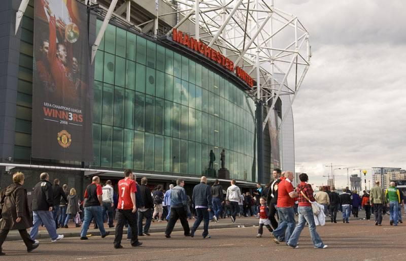 Football fans walk past Old Trafford Stadium