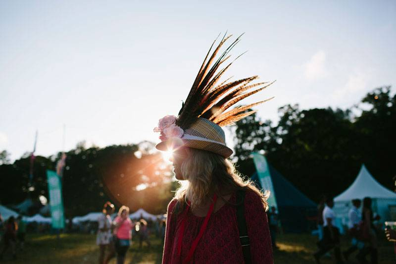 A reveller with feathers in her hat at Somersault Festival