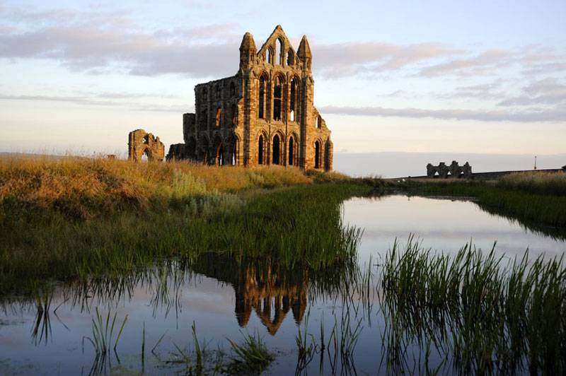 Whitby Abbey reflected in a lake © English Heritage