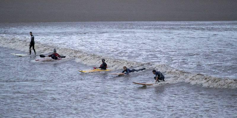 Surfers op de Severn Bore © VisitEngland