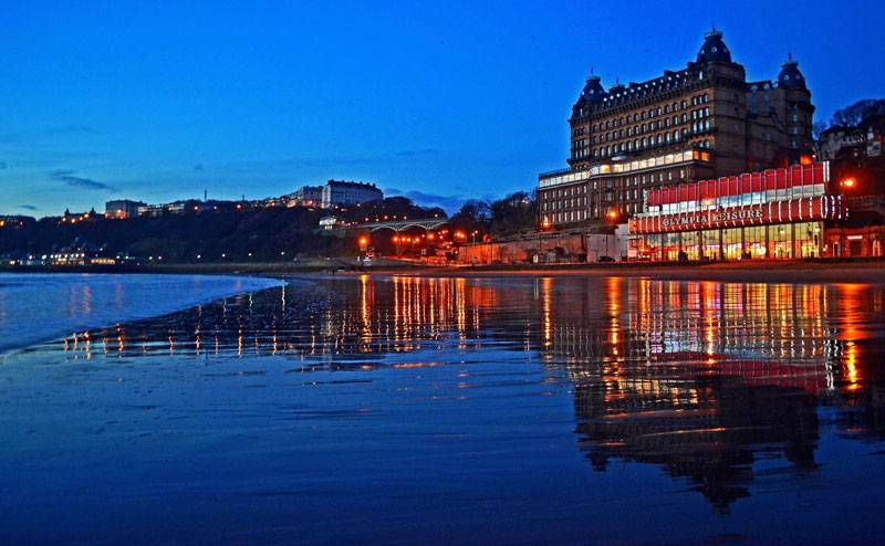 View of the Grand Hotel along the South Bay in Scarborough. Reflections on the beach.