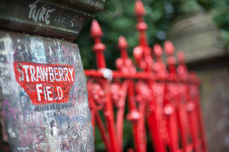 A close-up of the bright red Strawberry Field gate in Liverpool