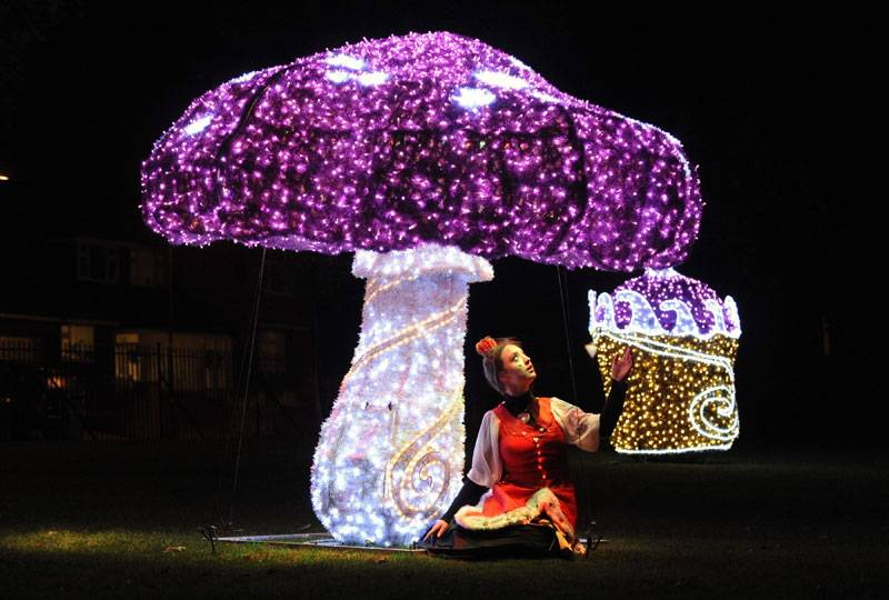 A woman dressed up as a fairy sits underneath a giant glowing purple mushroom
