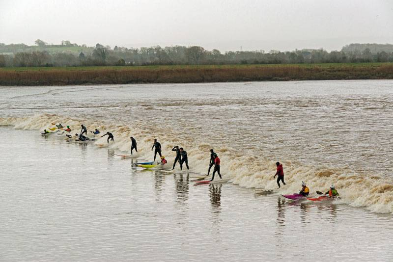 Surfers rides the waves on the vast River Severn