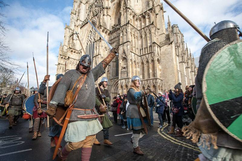 Viking performers armed with shields and swords parade past York Minster