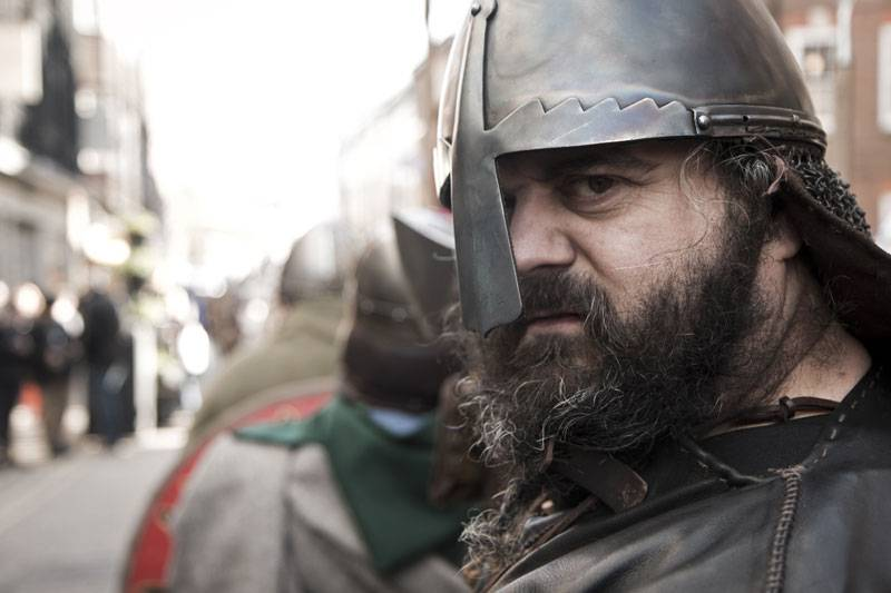 A close up of a man wearing a metal helmet look straight into the camera