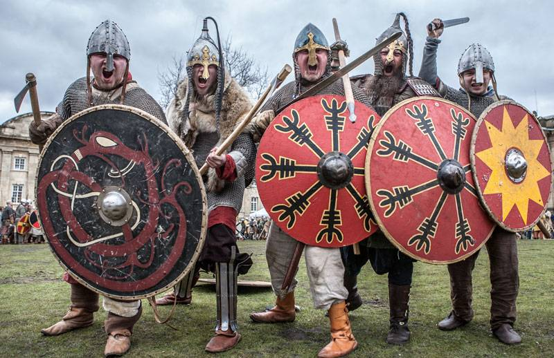 Viking warriors armed with colourful shields charge forwards as part of a re-enactment