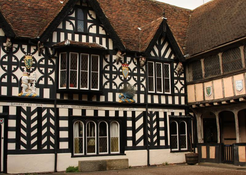 A half-timbered historic building in Warwick, decorated with coat of arms