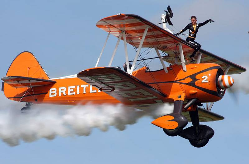A wingwalker performs a stunt on top of an airboune plane