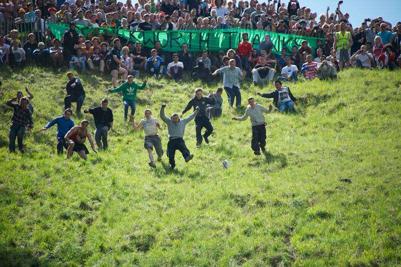 Cheese-chasing daredevils rolling down a steep hill at the Cotswolds Cheese Rolling Festival