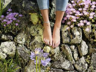 Bare feet rest on exotic plants in the Scilly Isles
