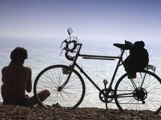 A cyclist takes a rest on a beach in Brighton