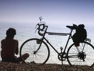 A cyclist takes a rest on a beach in Brighton