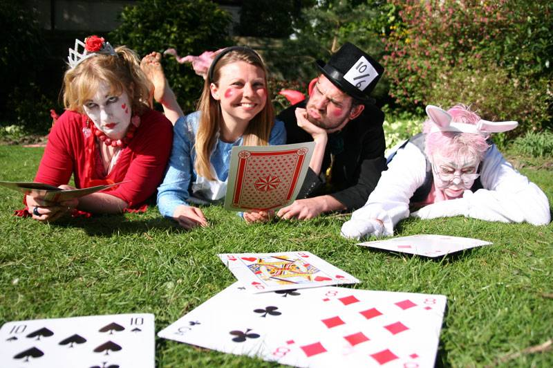 Costumed characters sit on a green lawn for Alice's Day