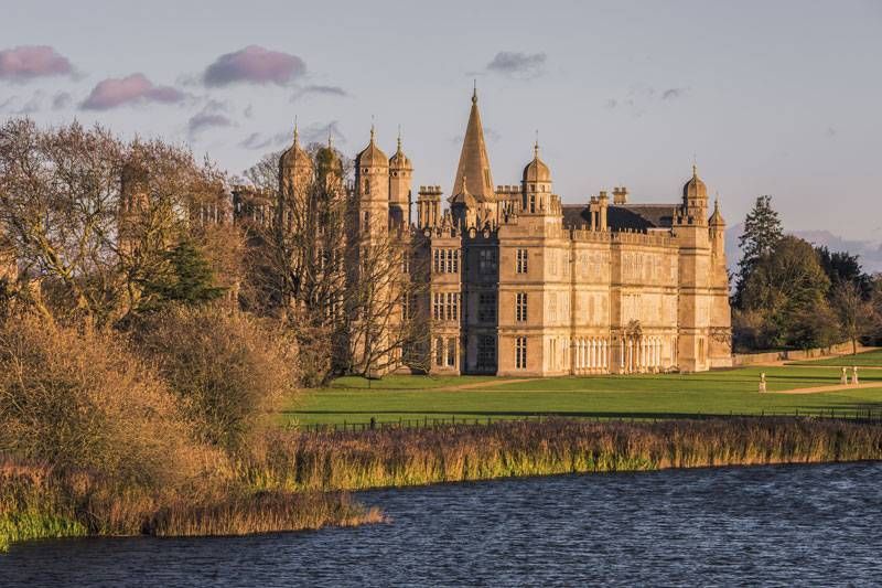 A view of the honey-hued Burghley House from across a vast lake