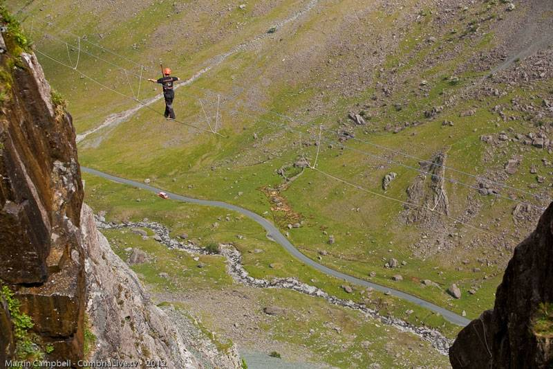 A climber suspended mid air between two cliffs on the Via Ferrata Extreme in Cumbria