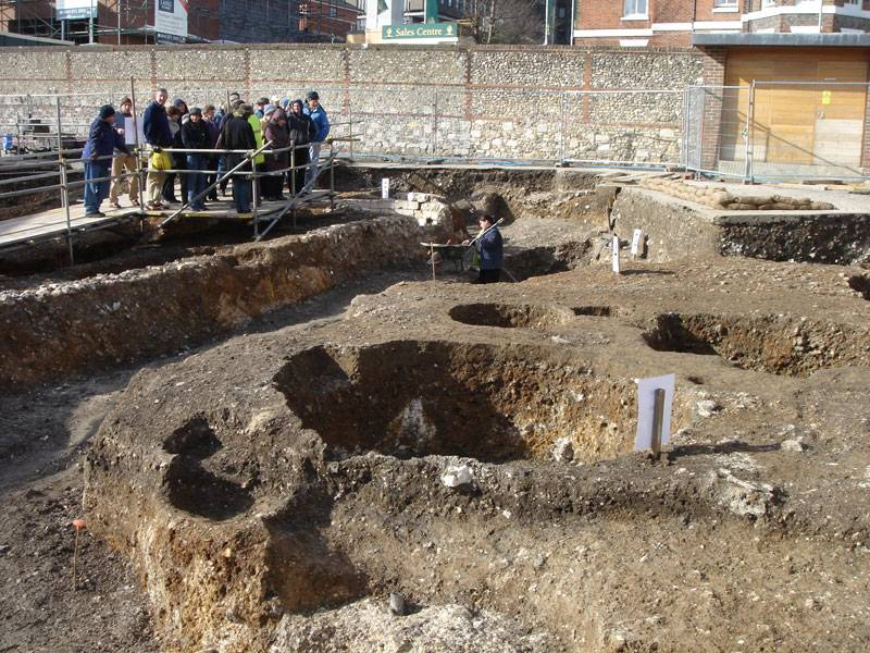 A group of visitors watch live excavations at Westgate in Oxford