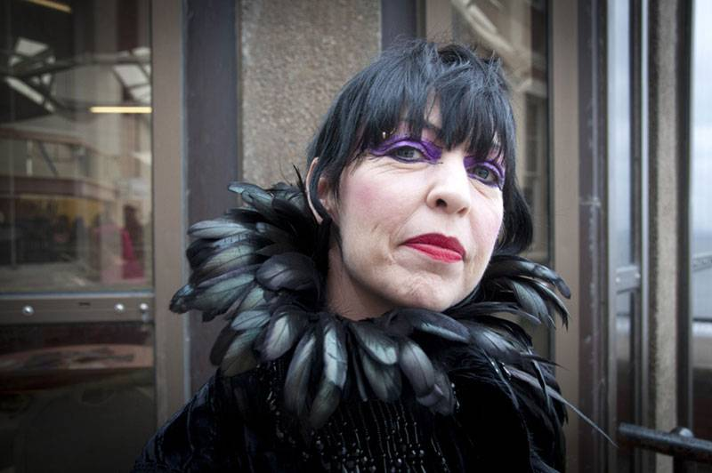 An elegant gothic lady with black hair, red lipstick and a trimmed feather cape at Whitby Goth Weekend