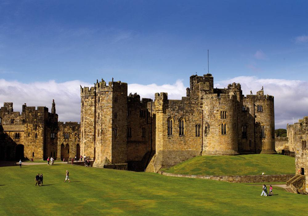 The towering turrets of Alnwick  Castle sit between a vast green lawn and clear blue skies