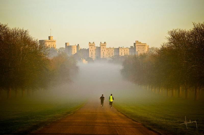 Windsor Great Park shrouded in mist as morning joggers head in the direction of Windsor Castle in the distance