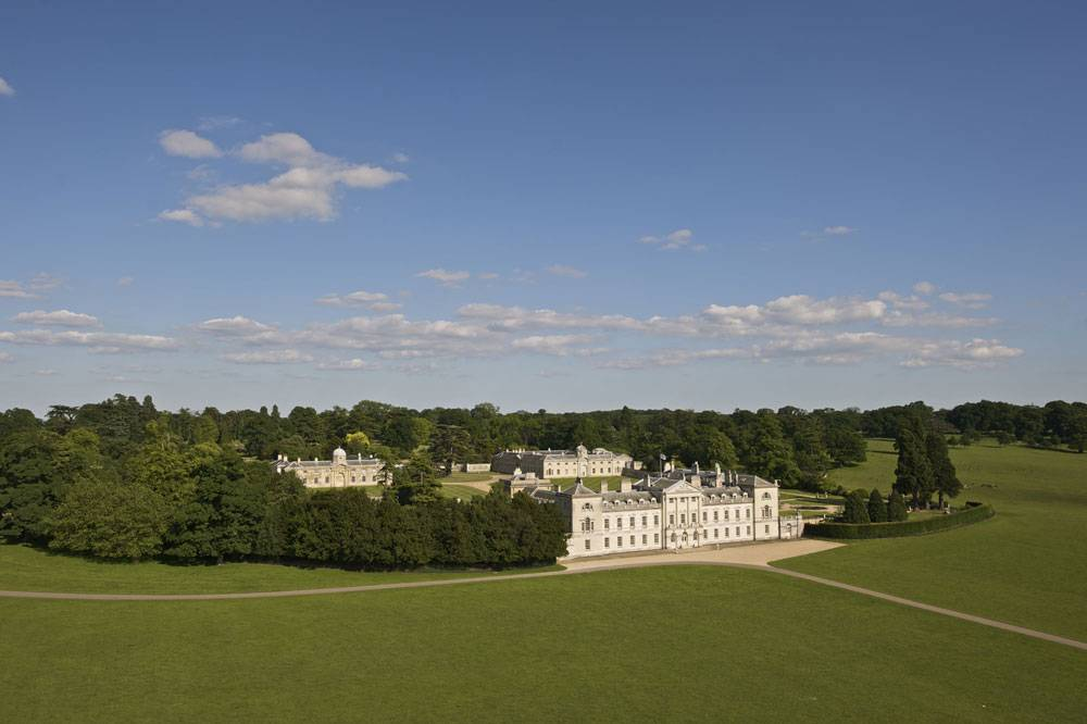 A bird's eye view of Woburn Abbey surrounded by green parkland