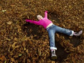 Child playing in the autumn leaves; NT Images John Millar