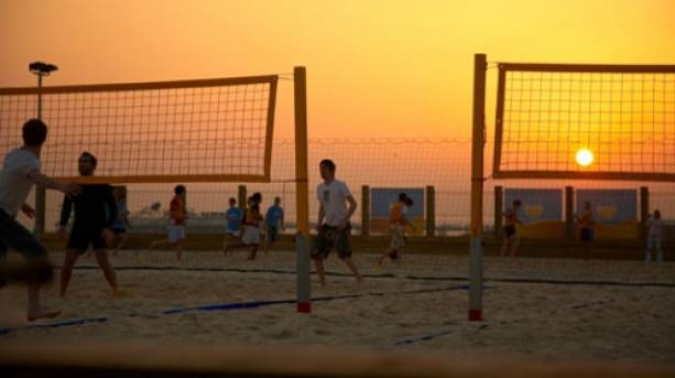 A photo of people playing beach volleyball at dusk at Yellowave Beach Sports.