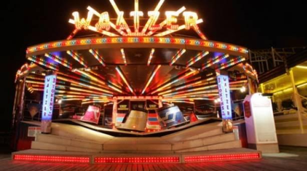 A waltzer ride on Brighton Pier at night.