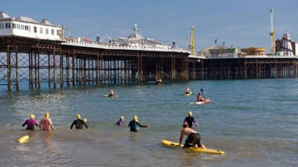 Swimmers in the sea next to Brighton Pier.