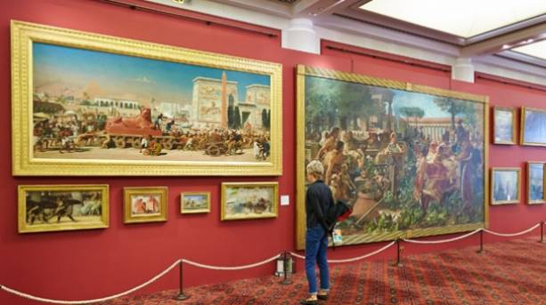 A visitor looking at paintings at Guildhall Art Gallery in London