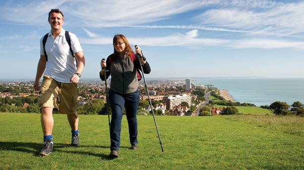 A couple walking from Eastbourne seafront onto the South Downs