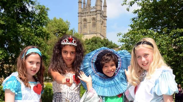 Children dressed up in Alice in Wonderland costumes in Oxford Botanic Gardens