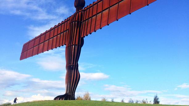 Person climbing hill to the Angel of the North