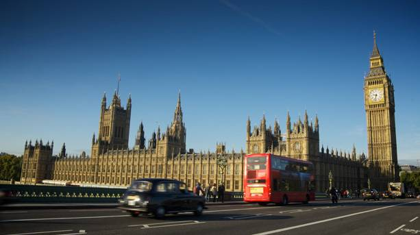The Houses of Parliament with red London bus and black cab hurtling past