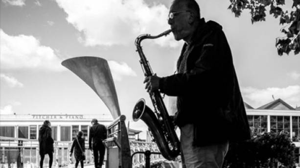 A busker playing the French horn