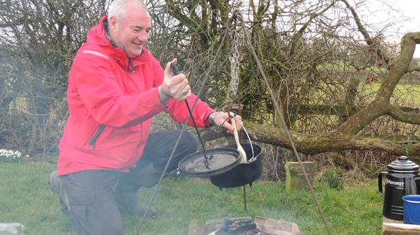 A man preparing food by an outdoor stove at Humblescough Farm, Lancashire